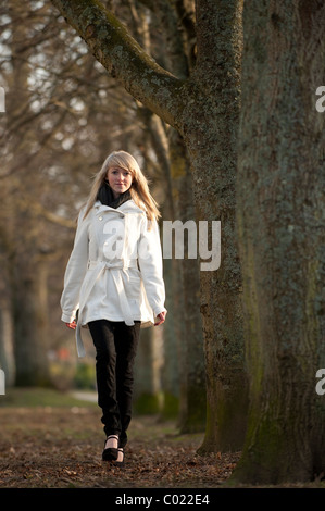 A slim blonde 14 year old teenage girl outdoors walking in a park on am autumn day, UK - Stock Photo