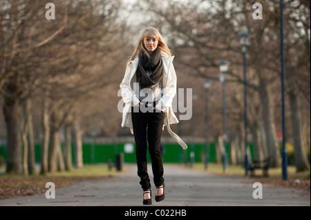 A slim blonde 14 year old teenage girl walking outdoors day UK - Stock Photo