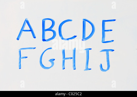 the letters A B C D E F G H I J in blue marker on a dry erase white board - Stock Photo