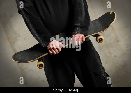 Mid section of man holding skateboard over concrete background with spotlight - Stock Photo