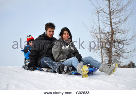 Hispanic immigrant family enjoying having fun in the first Winter snow - Stock Photo