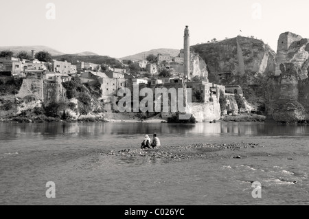Two people sitting on a sandbar in the Tigris River in the Kurdish town of Hasankeyf, in the southeast Anatolia - Stock Photo