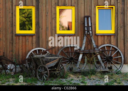 Old wooden wheels with pole and cart in front of a shed, Falkenstein near Donnersdorf, Lower Franconia, Bavaria, - Stock Photo