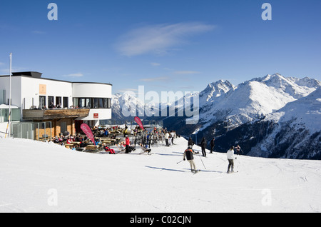 St Anton am Arleberg, Tyrol, Austria. Skiers on piste by Galzig gondola summit station with people sunbathing outside - Stock Photo