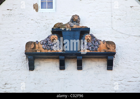 Three dimensional sign showing three lions on the wall of the former inn in the village of Holt, Wiltshire, England, - Stock Photo