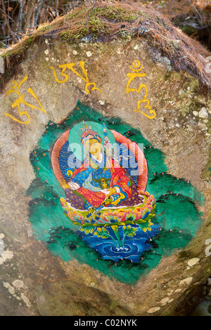 Painted Buddha image on a rock on the hiking trail to Taktsang Monastery, also known as Tiger's Nest, Paro, Bhutan - Stock Photo