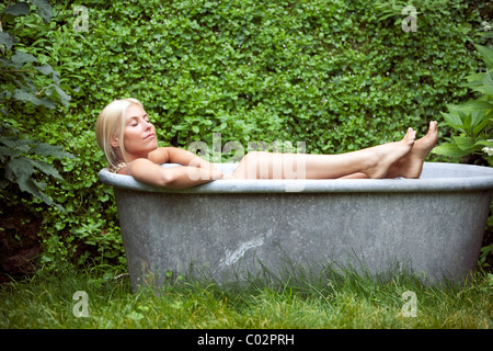woman in a bathtub in the garden - Stock Photo