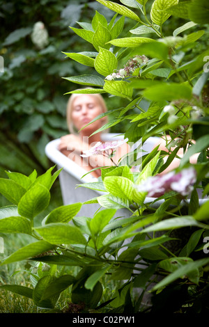 woman in basin in the garden - Stock Photo