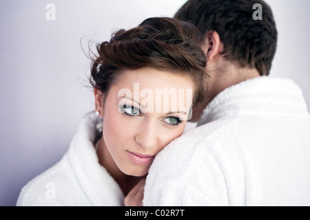 young woman and young man in bathrobe, hug - Stock Photo