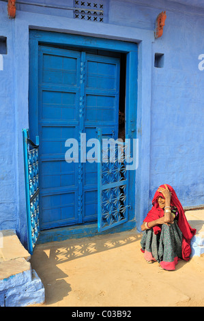 Elderly Indian woman wearing a red sari sitting on the floor in front of a blue-painted door, Thar Desert, Rajasthan, - Stock Photo
