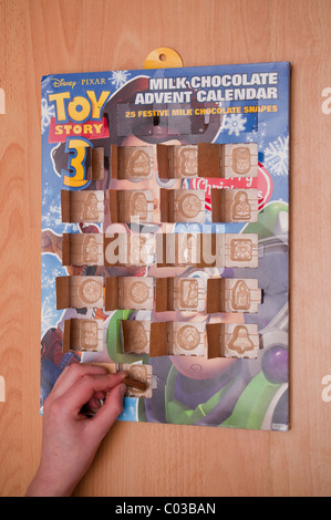 A MODEL RELEASED picture of an eleven year old boy opening the last window of an advent calendar on christmas day - Stock Photo