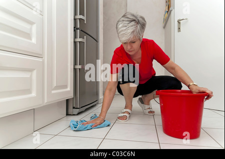 Woman squatting in the kitchen to wipe the floor - Stock Photo