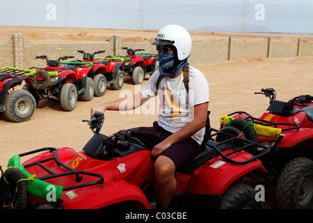 A man enjoys quad biking at Sharm el Sheikh in Egypt. - Stock Photo