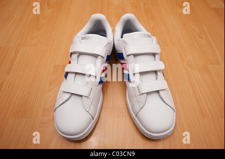A picture of a brand new pair of adidas velcro fastening for kids training shoes ( trainers ) - Stock Photo