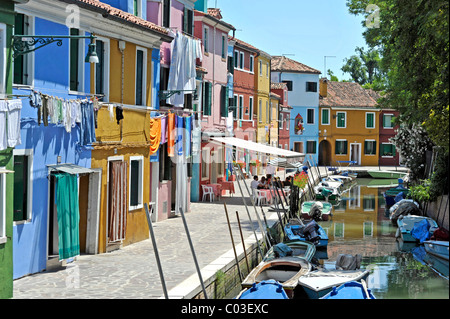 Canal with fishing boats in Burano, a village pub with tourists, fishermen's houses, Burano Island, Venice Lagoon, - Stock Photo