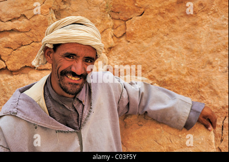 Portrait of a friendly man wearing a traditional djellaba and turban leaning against a rock wall, Todra Gorge, Morocco, - Stock Photo