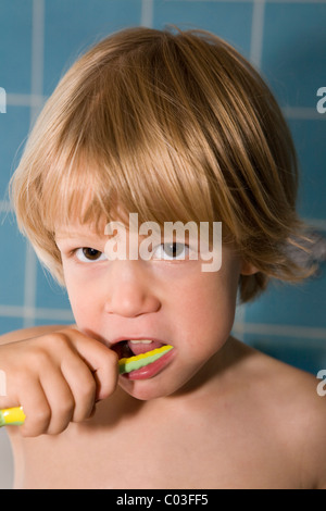 Four-year-old blond boy brushing his teeth - Stock Photo