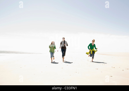 Woman and two children running on the beach of Amrum island, Schleswig-Holstein, Germany, Europe - Stock Photo