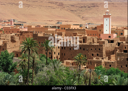 Typical village with traditional mud-brick houses and a mosque with a minaret in a date-palm oasis on Oued Todhra, - Stock Photo