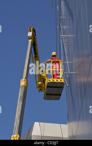 Worker wearing hard hat standing on an articulated telescoping boom lift near the top of a facade, worm's-eye view - Stock Photo
