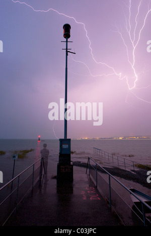 Thunderstorm with lightning and a storm warning light, man watching the thunderstorm while standing, Lake Constance, - Stock Photo