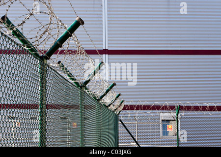 Barbed wire fence in front of a warehouse - Stock Photo
