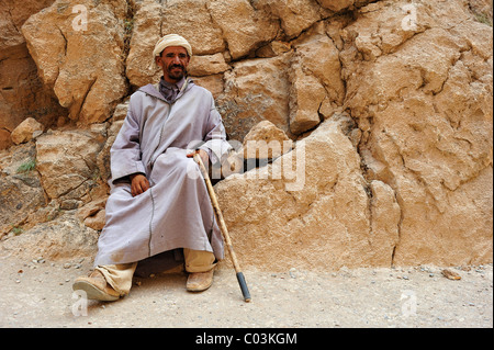 Elderly Berber man wearing a Djellaba and a turban leaning against a rock wall, Todra Gorge, Morocco, Africa - Stock Photo