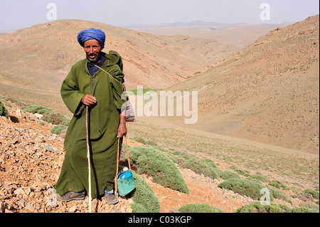 Goat shepherd, elderly man wearing a Djellaba and a turban, holding a water bottle, High Atlas Mountains, Morocco, - Stock Photo