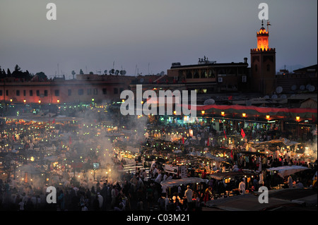 Evening at the Djemaa el Fna market square, literally meaning Assembly of the Dead, with smoke from the many food - Stock Photo