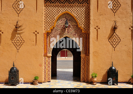 Entrance gate to a kasbah, mud fortress or residence of the Berber people with traditional tribal patterns, Southern - Stock Photo