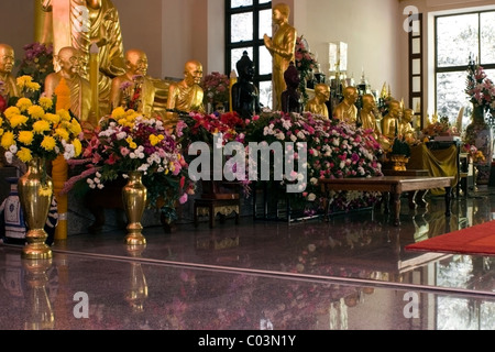 Several gold monk statues and colorul flowers are on display inside a Buddhist temple in Northern Thailand. - Stock Photo