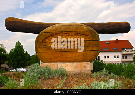 Wooden sculpture of a fried sausage, or Thuringian sausage, Holzhausen, Thuringia, Germany - Stock Photo