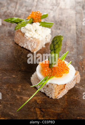 Luxury snack of bread and asparagus with eggs and red caviar - Stock Photo