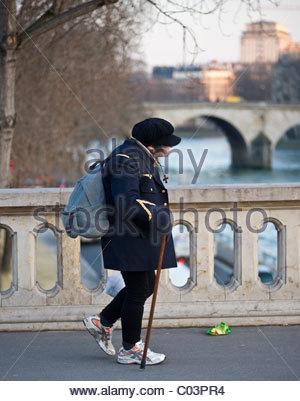 People walking - crossing a bridge over the River Seine Paris France - person walking across bridge OLD LADY STICK - Stock Photo