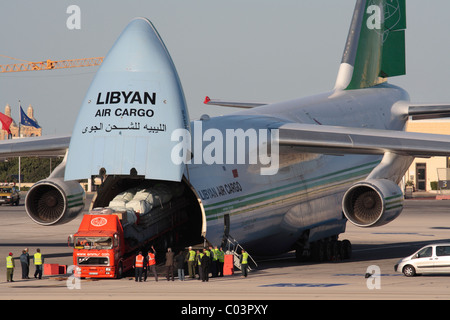 Loading cargo on board a Libyan Air Cargo Antonov An-124 by reversing a trailer truck into the aircraft - Stock Photo