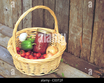 Basket of freshly picked organic vegetables and a jar of homemade salsa on a rustic background. - Stock Photo
