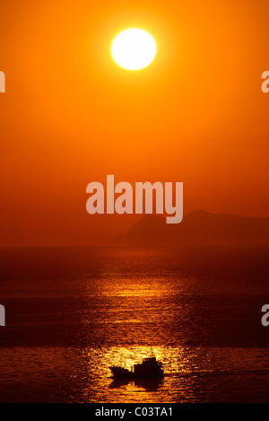 A fishing boat returning to Santorini around sunset. Photo taken from Oia village. Cyclades, Greece - Stock Photo