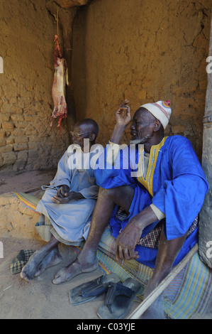 Two senior men in front of a slaughtered sheep at the Muslim festival of Tabaski. Dogon Country, Mali. - Stock Photo