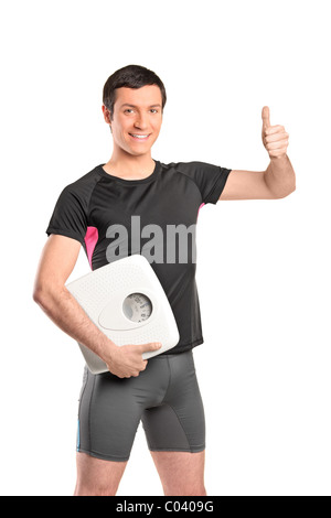 A happy young athlete holding a weight scale and giving thumb up - Stock Photo