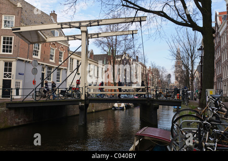 People crossing a bridge over a canal in Amsterdam - Stock Photo