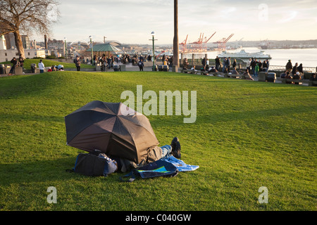 Man sleeping under an umbrella - Seattle, Washington - Stock Photo