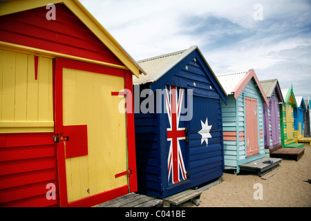 Brightly coloured wooden bathing huts line the beach at Brighton, Melbourne, Victoria, Australia - Stock Photo