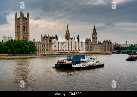 Dramatic cloudy day view of ship traffic and Parliament on the River Thames and in London, England. - Stock Photo