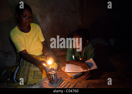 A mother lights a small lamp for her child to study by in Masaka, Uganda, East Africa. - Stock Photo