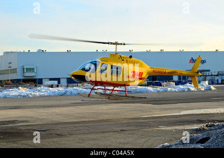 Bell 206 helicopter in DHL livery landing at New York's JFK airport to collect documents for delivery to Manhattan's - Stock Photo