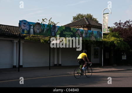 London Zoo sign, Zoological Gardens entrance and biker in yellow t-shirt, Regents Park, England, UK, Europe, EU - Stock Photo