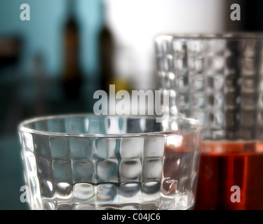 glasses of red drink and bottles in the background - Stock Photo