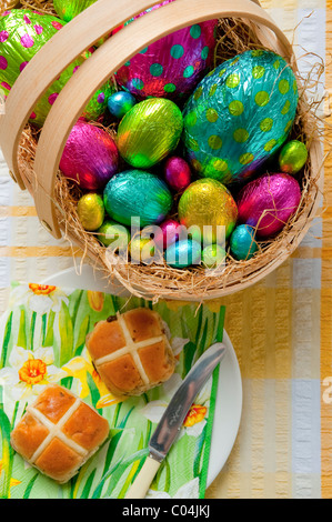 wooden basket filled with colorful foil wrapped chocolate easter eggs on yellow and white tablecloth Hot cross buns - Stock Photo