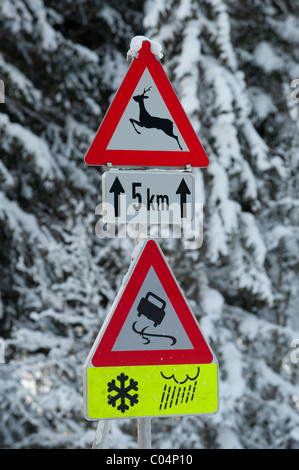 traffic sign warns at winter of snow and ice on slippery road - Stock Photo