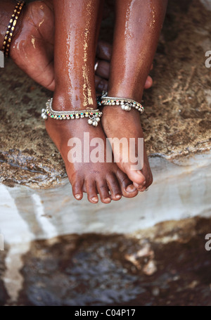 Mother washing her child feet Andhra Pradesh South India - Stock Photo